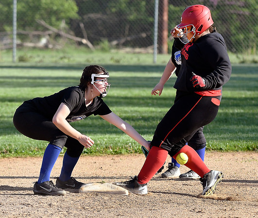 John P. Cleary | The Herald Bulletin <br /> APA's Christine Klepfer tries to field the ball as it goes in between Liberty Christian base runner Gianna Thigpen as she runs to second base on a past ball in the third inning of their game Monday evening.