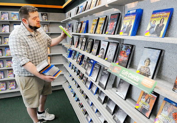 Don Knight | The Herald Bulletin<br /> Family Video manager Rob Young puts movies out on the shelf at the location on 38th Street on Monday.