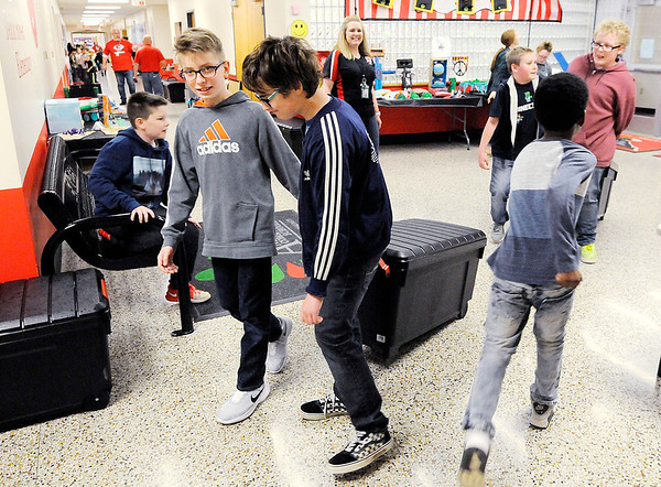 Don Knight | The Herald Bulletin<br /> From left, Elijah Johnson and Aiden Williams move a tote full of food at Tenth Street Elementary on Thursday.