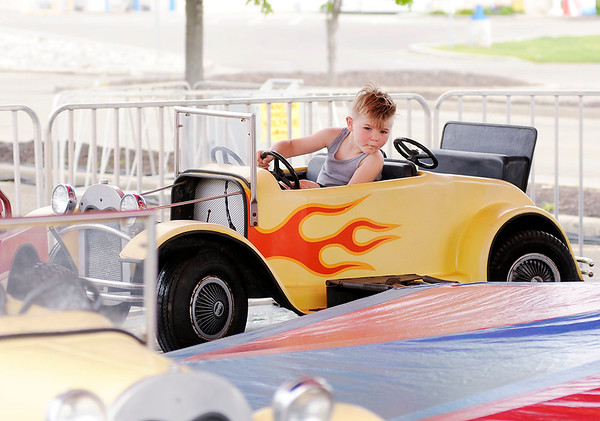 Don Knight | The Herald Bulletin Kage Gullion, 4, from Frankton rides a hot rod carousel during the Little 500 Festival Fair at the Applewood Center on Wednesday.  The festival will be open 5 to 11 p.m. on Friday, 3 to 11 p.m. on Saturday and 3 to 10 p.m. on Sunday. Wristbands are $20 and the festival is located in front of the former Target location.