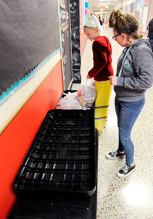 Don Knight | The Herald Bulletin<br /> From left, Cora Roper and Addisyn Orbik count food bags for distribution to classes at Tenth Street Elementary on Thursday.