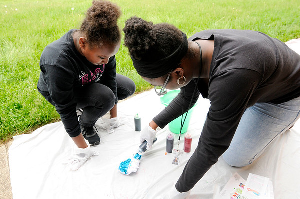 Don Knight   The Herald Bulletin<br /> Deborah Gardner, right, helps Sanae Turner tie dye a T-shirt during a meeting of the  Edge Club at Edgewood Elementary on Friday.