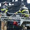 Don Knight | The Herald Bulletin<br /> Firefighters perch on the the ladder of  a Noblesville fire truck as they overhaul a fire scene at 119 Franklin in Pendleton on Tuesday.