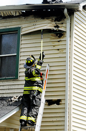 Don Knight | The Herald Bulletin<br /> A firefighter removes vinyl siding searching for hotspots after a house fire at 119 Franklin in Pendleton on Tuesday.