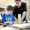 Don Knight | The Herald Bulletin<br /> Trenton Parrish tightens the bolts on a brake pedal with some help from Daniel Etherington during a Soap Box Derby workshop at the Geater Center on Thursday.