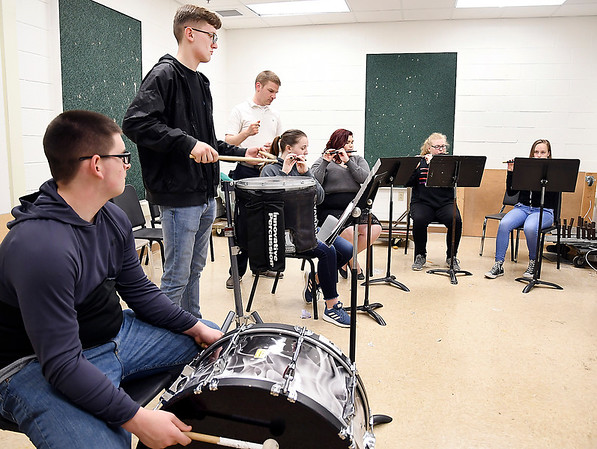 John P. Cleary | The Herald Bulletin <br /> Anderson High School marching band director Richard Geisler, background, works with members of the fife and drum corps as they practice for an upcoming show.