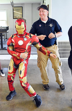 "John P. Cleary | The Herald Bulletin <br /> Anderson Police officer Eric Holtzleiter keeps time with the music as Alexander ""Iron Man"" Williams, 13, shows off  his dance moves during the annual Highland Middle School Life Skills class outing Wednesday at the FOP lodge.  event with the theme of ""Super Heroes."" Holtzleiter and fellow officer Chad Purciful started the event seven years ago and it continues to grow each year."