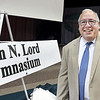 John P. Cleary | The Herald Bulletin<br /> Maple Ridge Elementary School principal John Lord stands next to the new gym sign Thursday as the facility was dedicated in his name for his retirement after 41 years in education.