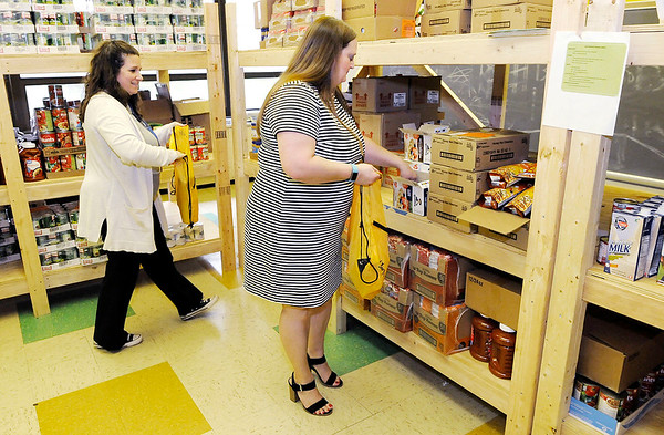 Don Knight | The Herald Bulletin<br /> From left, Amy Gill and Brooke Carrell load backpacks with food from APA's food pantry to be sent home with kids on Thursday.