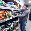 Marty Spivey-Bevington checks the bulk pet food section of 2Guyz Boutique for Pets in Elwood as they are gradually re-opening for business after closing last month on Gov. Eric Holcomb's executive order.