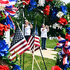 """Framed in a memorial wreath, Kevin and Lucinda Rushton play Taps at Maplewood Cemetery's veterans section Memorial Day morning. The Rushtons are members of Taps For Veterans and were visiting several cemeteries in the area to take part in """"Taps Across America"""" for our fallen veterans on this holiday."""