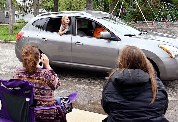 Summitville Elementary first-grader Evelyn VanMatre leans out the window as she says goodbye to teachers Tasha Walls and Caitlin Dauby as her family drives by the school for the Tuesday meal distribution pickup. Madison-Grant School Corp. teachers greeted students as a way to help close out the school year and say goodbye to them.