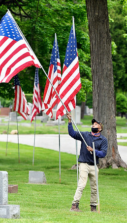 Mapelwood Cemetery employee Marzell Stennis unfurls this American flag as he puts it up on the cemetery grounds Wednesday morning. The cemetery is preparing decorations for the upcoming Memorial Day holiday by putting up hundreds of American flags that line the driveways of the facility.