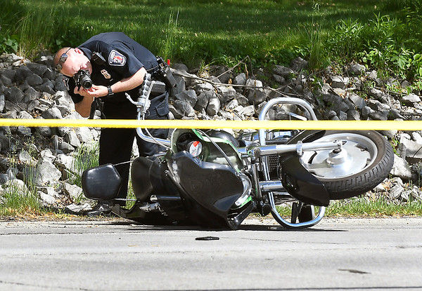 An investigator from the Anderson Police Department photographs the scene of an accident Friday afternoon in the 3400 block of South Scatterfield Road in which the Madison County Coroner Danielle Dunnichay-Noone confirmed there was one fatality as a result of the crash.