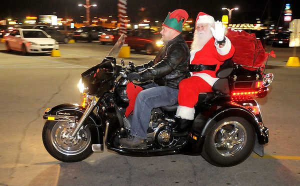 Santa arrives at Mounds Mall on a custom Harley-Davidson trike driven by Chris Mishler on Saturday.