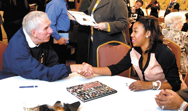 One tennis great meets another as Bill Harless and Ashlee Davis greet each other at a public reception and book signing Tuesday evening for the 100 Greatest Athletes book that they are a part of at the Anderson Center for the Arts.