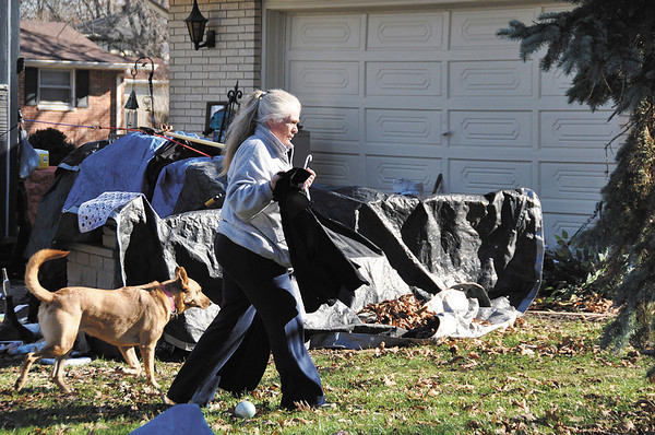 Peggy Kruse and her dog Pancho walk by the driveway outside Kruse's home. She is carrying clothes that had been hanging from a truck's door; she said the clothes had been drying in the sunlight.