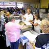 Volunteers work the serving line during the Gospel Hightlight Radio Broadcast 30th Annual Community Thanksgiving Day Dinner at the Geater Community Center on Thursday.