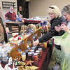 From right, Elaine Pigg and Joyce Taylor check out the candles being sold by Sandra Brizendine during the Madison County Humane Society's 34th annual Christmas and Hobby Show at the Rangeline Community Center on Saturday.