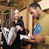 Susan Lester and DeJovaun Sawyer-Davis look over the 100 Greatest Athletes book that they are a part of at a public reception and book signing Tuesday evening at the Anderson Center for the Arts.