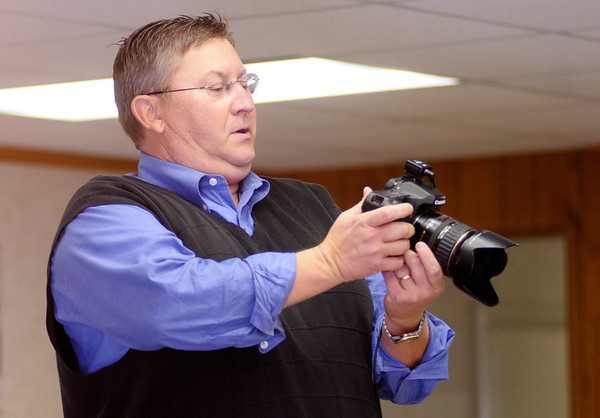 Local photographer Brian Taylor checks a photo on the LCD screen of his camera while taking a family portrait of the Williamson family during their Thanksgiving reunion. Taylor and his father before him have been photographing the Williamson family Thanksgiving portrait for 40 years.