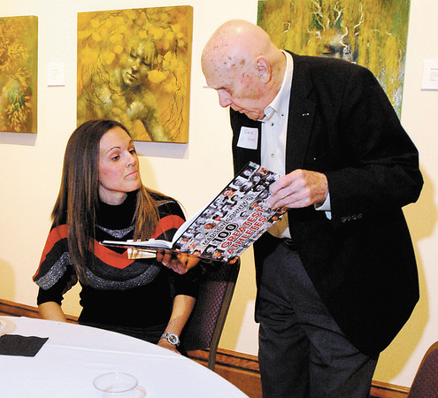 Angel Hall and Gene Yates look over the 100 Greatest Athletes book that they are a part of at a public reception and book signing Tuesday evening at the Anderson Center for the Arts.
