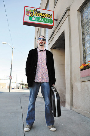 Troy Burk stands outside of Stingers in Elwood, one of his favorite local places to play.