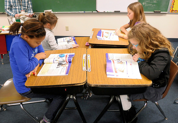 Clockwise from left, Quinlyn Byrd, Madalynn Mercer, Brooklynn Hogge and Cydnie Layton follow along in their text books as Doug Beisley teaches a lesson on George Washington at Liberty Christian on Thursday.