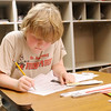 Shane Delmolino gets started on his homework as students wait for the final bell at the end of the school day at Liberty Christian on Thursday.