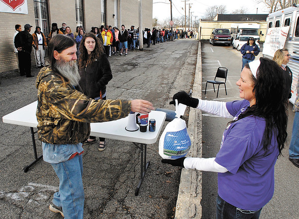 Jimmy Marsh receives a turkey from Christa Conway of the Quarter Horse Racing Association of Indiana Monday as they gave away 100 frozen birds to those who showed up at the Salvation Army parking lot.