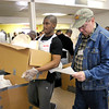 Grant Steans carries out a box of meals for delivery driver Gail Laymen during the Gospel Hightlight Radio Broadcast 30th Annual Community Thanksgiving Day Dinner at the Geater Community Center on Thursday. Helping Laymen to deliver those meals was Martez Alexander.