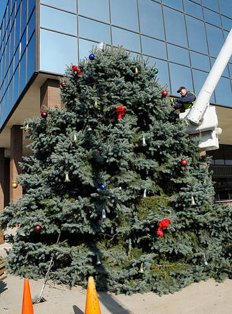 Ryan Morgan secures a silver bell to the county Christmas tree outside the Madison County Government Center on Friday. This year's tree was donated by John and Elaine Gray of Pendleton. Also helping to decorate the tree were Amy Dillon, Jenny Jackson and Rick Smith.