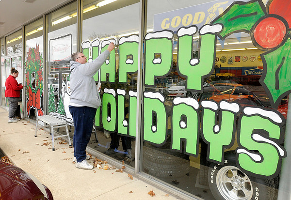 Eric Murphy and his daughter Shelby, 13, decorate the windows at T&J Tire for the holidays. Murphy started painting windows when he was 13. He now has several regular holiday clients in the area.