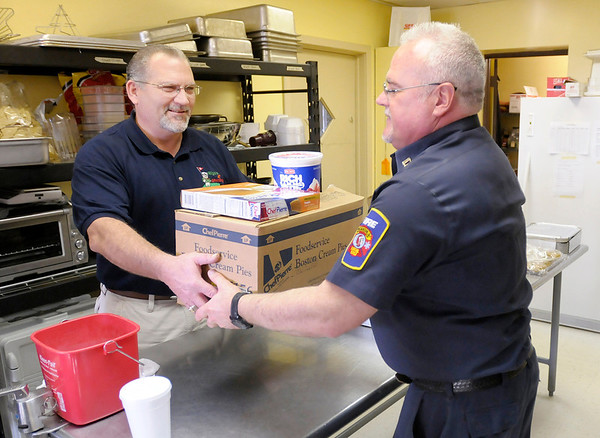 """Cpt. Robin Branch, right, from Station 1 picks up a Thanksgiving meal for his fire station from John Rigsby at Rigo's at Grandview on Thursday. The restaurant provided Thanksgiving meals for Man 4 Man, Stepping Stones and the city's firefighters working on the holiday.  Rigsby, a co-owner of the restaurant, said,""""We've been very blessed here as a new business and we wanted to share that with the community."""""""