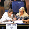 Poll workers Gloria Bowman and Julie Foltz record absentee ballots into the poll book as Ed bowman gets the voting machines setup Monday evening at Park Place Church of God in preparation for election day Tuesday.