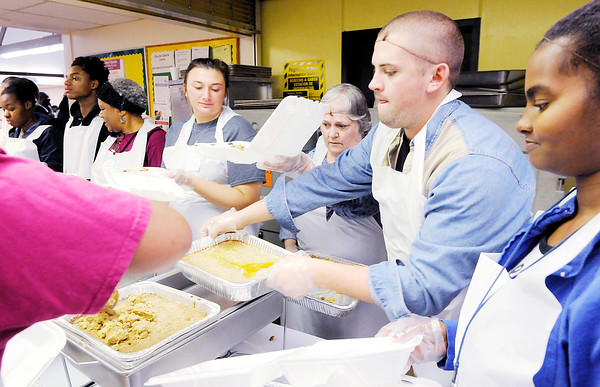 Don Knight | The Herald Bulletin<br /> David Archer replenishes the stuffing on the serving line at The Gospel Highlights Radio Broadcast 34th Annual Community Thanksgiving Day Dinner at the Geater Community Center on Thursday.