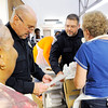 Don Knight   The Herald Bulletin<br /> APD officers Randy Doss, left, and Rod Hagerman look over the delivery route during The Gospel Highlights Radio Broadcast 34th Annual community Thanksgiving Day Dinner at the Geater Community Center on Thursday.