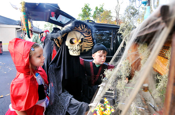 John P. Cleary |  The Herald Bulletin<br /> Lydia Schmitt, 7, and brother Peter Schmitt, 6, check out this piano-playing skeleton during the Trunk-and-Treat at the Anderson Moose Lodge #150 Halloween night. The spooky display was created by Lisa Moore and Daniel Thompson.