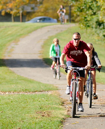 Don Knight | The Herald Bulletin<br /> Bicyclists ride on the trail past Killbuck Wetlands on Saturday. Several people visited local parks to enjoy the unseasonably warm weather.