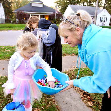 John P. Cleary    The Herald Bulletin<br /> Emersyn Rhoton, 4, gets some candy from Stachia Myers as Londyn Widener, 8, and Riddick Allison, 9, background, check out each others goodies while trick-or-treating along Crystal Street in North Anderson Monday evening.