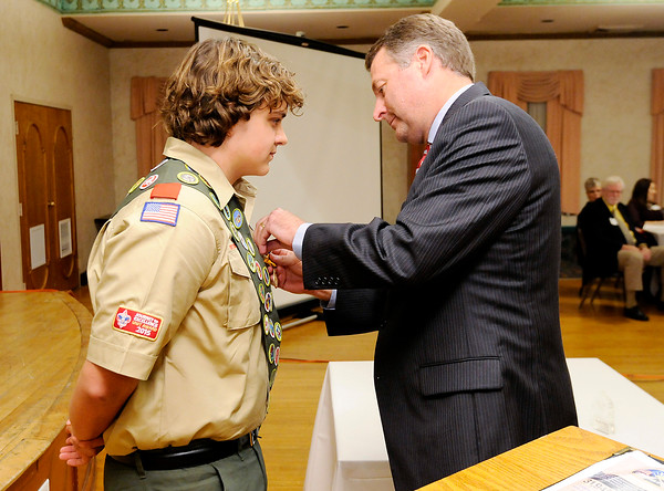 Don Knight | The Herald Bulletin<br /> Crossroads of America Council CEO Patrick Sterrett pins the Medal of Merit on Tanner King during the Madison County Distinguished Citizens awards dinner at the Paramount on Wednesday. The medal is one of scouting's highest honors and was awarded to Tanner for his action and bravery rescuing a 10-year-old girl who fell through the ice on the White River in 2015.
