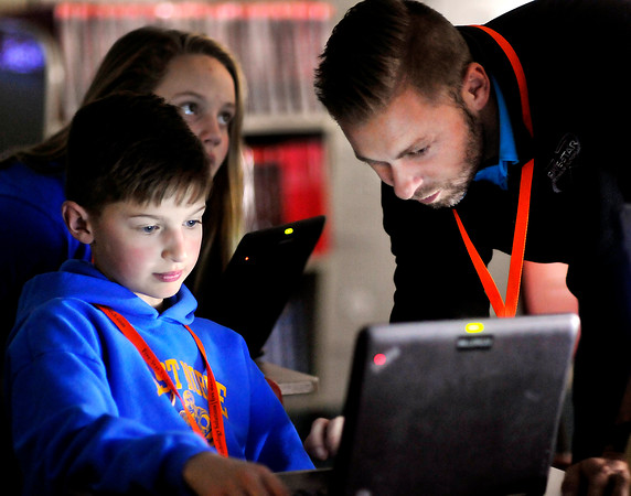John P. Cleary |  The Herald Bulletin<br /> by the glow of his computer Carver Miller, 11, a 6th grader from East Noble School Corp., gets some assistance from Adam Cole, a professional learning specialist at Five Star Technology Solutions, during his breakout session titled: Proms, Yearbook, Science... and Google Forms? at the second annual fall Hoosier Student Digital Leaders summit held at Elwood Jr.-Sr. High School Tuesday.