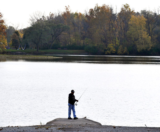 John P. Cleary    The Herald Bulletin<br /> The evening sky reflecting off the water silhouettes this angler as he fishes off the boat ramp at the north end of Shadyside Lake.