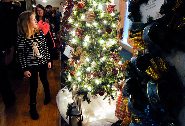 """Don Knight   The Herald Bulletin<br /> Sydney Thompson, 10 looks at a tree titled """"Old Fashioned Christmas"""" and designed by Susan Davenport and Susan Lawrence during the Festival of Trees at the Paramount on Saturday. Saturday was the first day the display of trees was open to the general public. It is open today from noon to 5 p.m."""