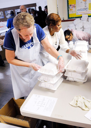 Don Knight | The Herald Bulletin<br /> Pamela Youngblood, right, counts meals as Karen Ramey loads them into boxes for delivery by APD officers Randy Doss and Rod Hagerman during The Gospel Highlights Radio Broadcast 34th Annual Community Thanksgiving Day Dinner at the Geater Community Center on Thursday.