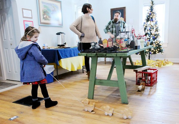 Don Knight   The Herald Bulletin<br /> Ada Rodocker, 5, plays with a set of wooden ducks as her parents Andrew and Heather shop the Small Business Saturday Sale at Park Place Arts. The sale featured the work of local artists.