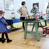 Don Knight | The Herald Bulletin<br /> Ada Rodocker, 5, plays with a set of wooden ducks as her parents Andrew and Heather shop the Small Business Saturday Sale at Park Place Arts. The sale featured the work of local artists.