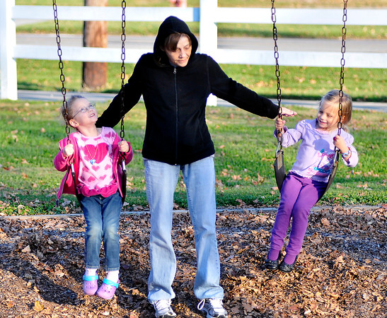 John P. Cleary |  The Herald Bulletin<br /> Debbie Armstrong, center, pushes Dee Brown, 5, and   Mackenzie Troxell, 3, together as they enjoy the warm November weather while playing at Millcreek Park in Chesterfield Tuesday afternoon.