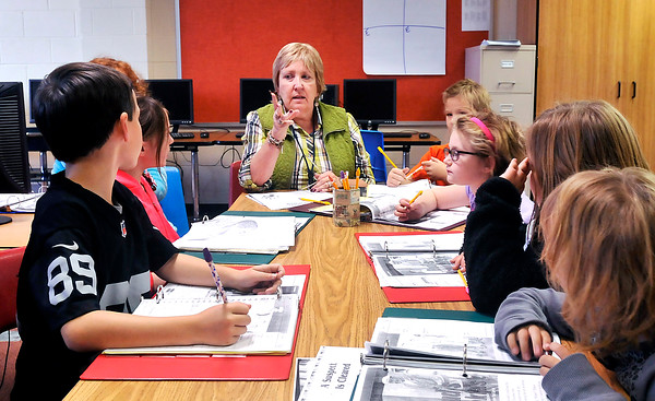 John P. Cleary |  The Herald Bulletin<br /> Elwood Intermediate School teacher Mary Ellen Whitson discusses the days lesson with her students in the Read 180 program after school this past week. The reading program is part of the after-school intervention program at the school.