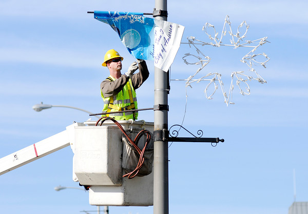 Don Knight   The Herald Bulletin<br /> John Binda hangs banners for the holiday season on the Eisenhower Bridge on Friday. The city will have a tree lighting and Christmas parade on December 2nd at 7p.m.